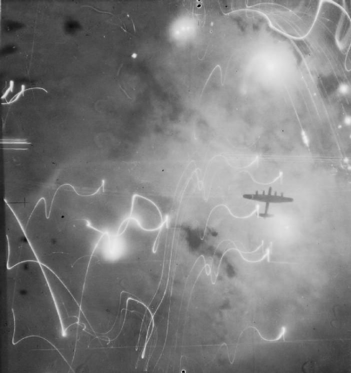 An Avro Lancaster of No. 1 Group, Bomber Command, silhouetted against flares, smoke and explosions during the attack on Hamburg, Germany, by aircraft of Nos. 1, 5 and 8 Groups on the night of 30/31 January 1943