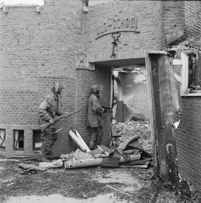 A Dutch school damaged by mortar fire, being searched for German snipers by Sergeant J Whawell and Sergeant J Turrell of the Glider Pilot Regiment.