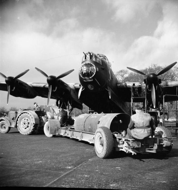 An 8,000-lb HC bomb ('super cookie') is brought by tractor to a waiting Avro Lancaster of No. 106 Squadron RAF in its dispersal atSyerston, Nottinghamshire.