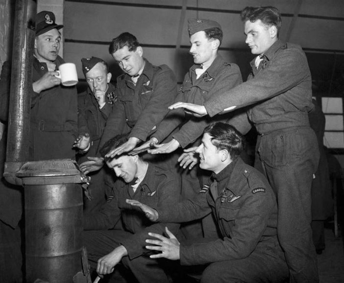 "The crew of Lancaster ""C for Charlie"" of No 44 Squadron try to warm themselves in their Nissen hut quarters at Dunholme Lodge, after returning from a raid on Stuttgart, 2 March 1944."