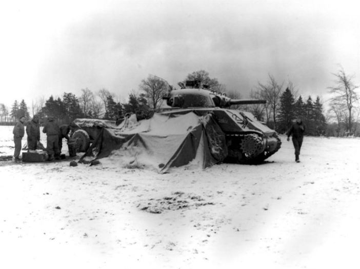 Battle of the bulge - Tankmen of the U.S. First Army gather around a fire on the snow-covered ground near Eupen, Belgium, opening their Christmas packages (12/30/44) -5th Armd. Regt