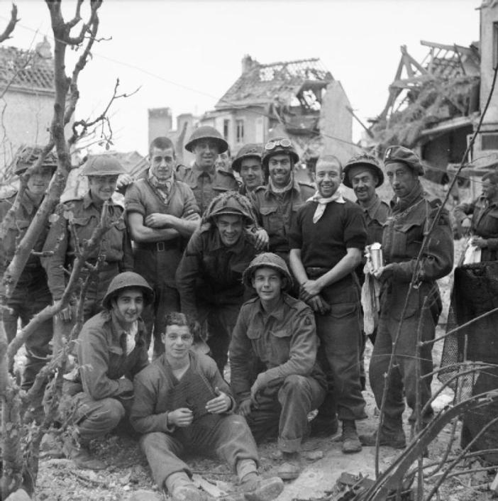 A cheerful group of soldiers from 3rd Division pose for a photograph in Caen, 10 July 1944.