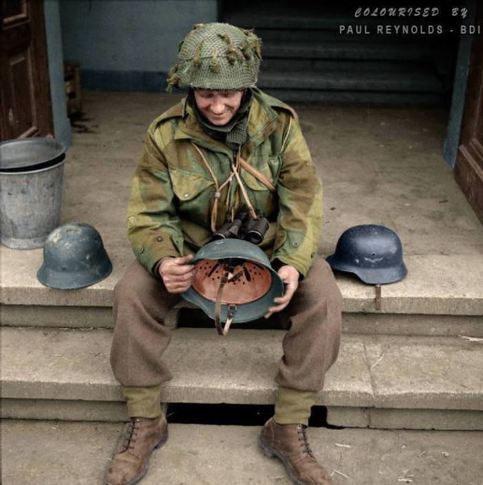 Regimental Sergeant Major Evans of the 12th Battalion, The Devonshire Regiment examines captured German helmets in Hamminkeln, Germany, 25th March 1945.