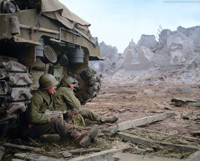 US 3AD soldiers, Cpl. James L. Gregory and T/5 Omer G. Taylor of 'C' Company, 1st Battalion, 36th Armored Infantry Regiment, 3rd Armored Division seek shelter behind a M-4 Sherman tank while under German Artillery bombardment at Geich, near Düren, Germany, on the 11th of December 1944.