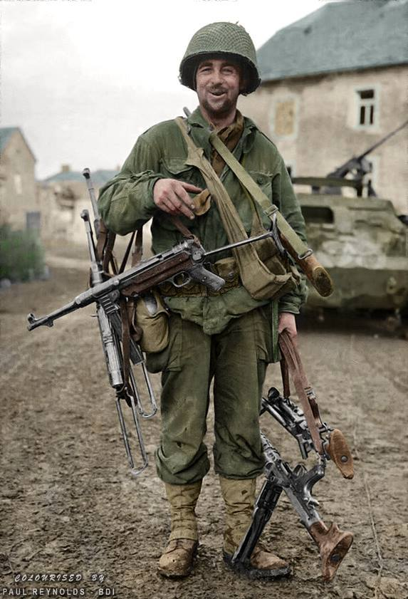 "This photo was on the cover of 'YANK' Magazine, Continental Edition of January 14, 1945, entitled ""PRESENT ARMS"" it featured Pfc. Robert Leigh and his collection of enemy weapons taken by the 83rd Infantry Division during the Battle of the Hürtgen Forest. (MP.38 and MP.40's, an MG.34 and an MG42)"