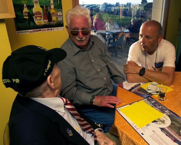 "Airborne veteran James ""Pee Wee"" Martin, left, shares his experience of his parachute landing during D-Day with Erich Bessoir, a former German Waffen-SS soldier, while amateur historian Bert Brimks translates June 7, 2014, at Omaha Beach, in Normandy, France. The veterans and former enemies, spent the evening together, exchanging experiences and memories of their fight in Normandy, in 1944. (Credits: Alexander W. Riedel)"