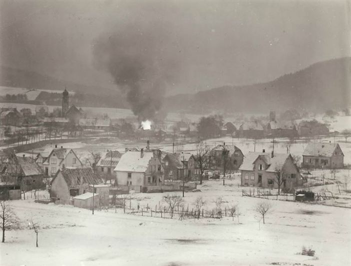 American forces are trying to recapture this German town (unknown) from German mountain troops who infiltrated it during the night, dislodging American troops and taking a number of Prisoners. Hotel 'Wenk' and Gasoline are in yard and hit by a tracer bullet, resulting in the burning, as seen in photograph. In the church tower on the left is a German lookout, who is also sniping at the U.S. soldiers.