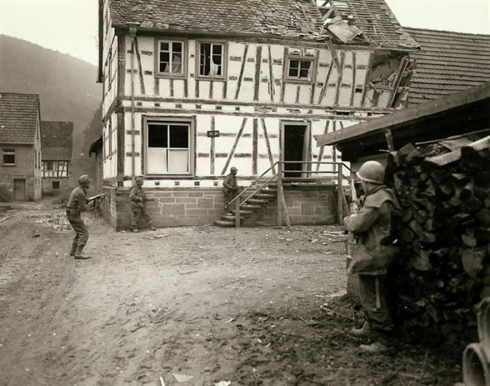 Seventh Army men looking for snipers in a German town.