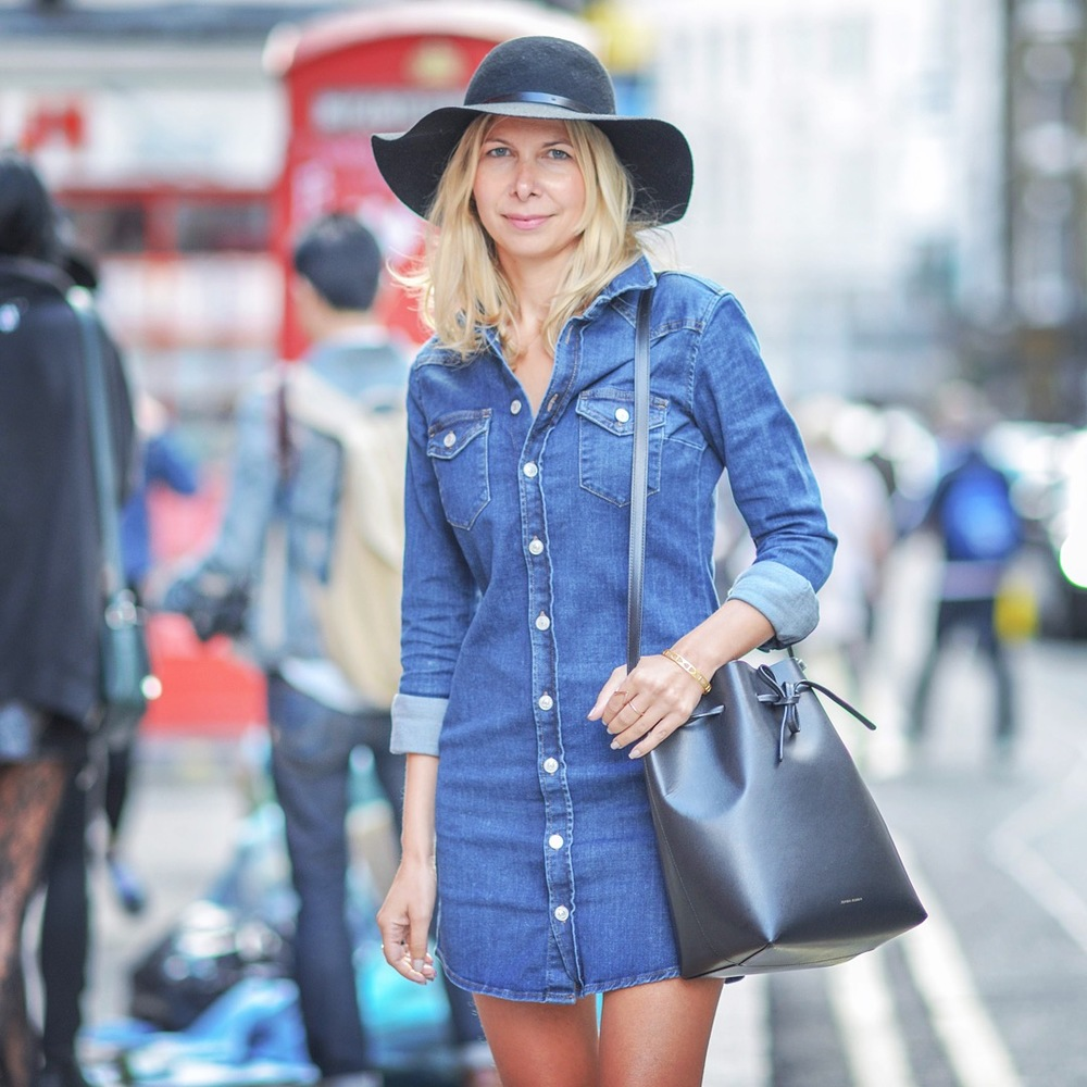 Wearing Topshop Denim dress, Russell & Bromley boots, Mansur Gavriel bucket bag and Topshop hat during London Fashion Week.  Image via London Portraits