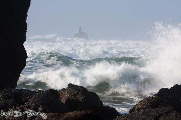 Waves crash before the Tillamook lighthouse in the distance