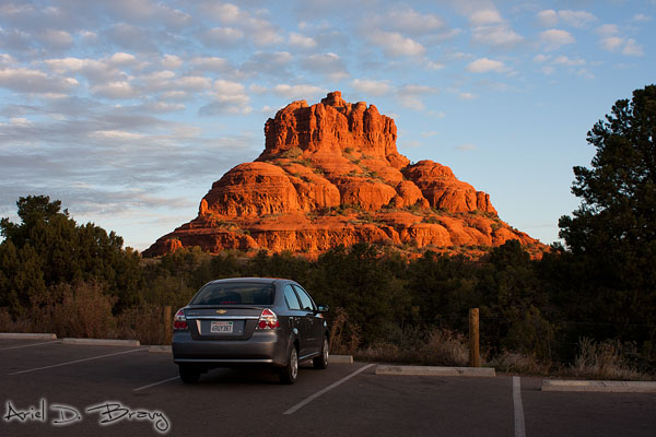 Rental car in front of Bell Rock at sunrise
