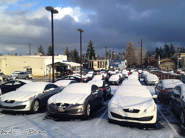 The clouds break to let the sun shine on the snow-covered cars