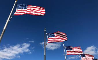 american flags flapping with blue sky background