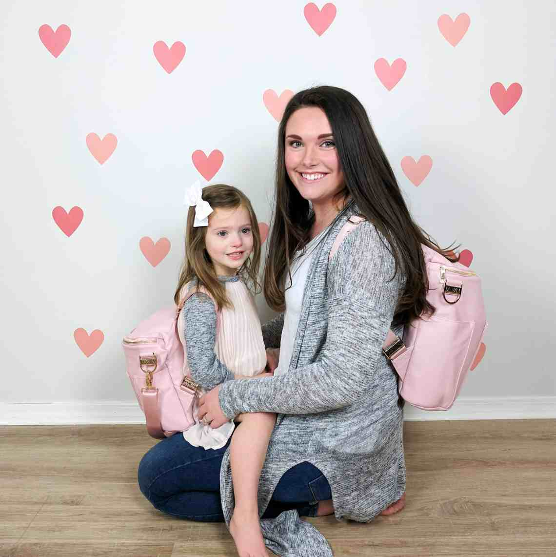 mom and daughter with matching pink bags in front of heart wall