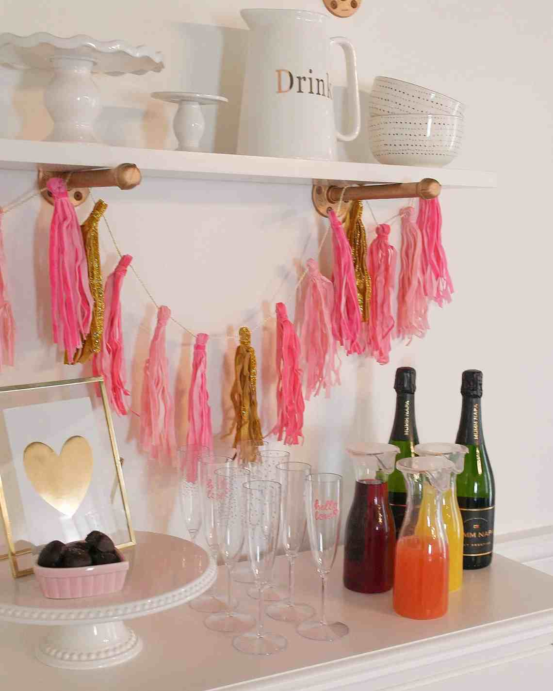 pink banner, juice, champagne on white chest of drawers