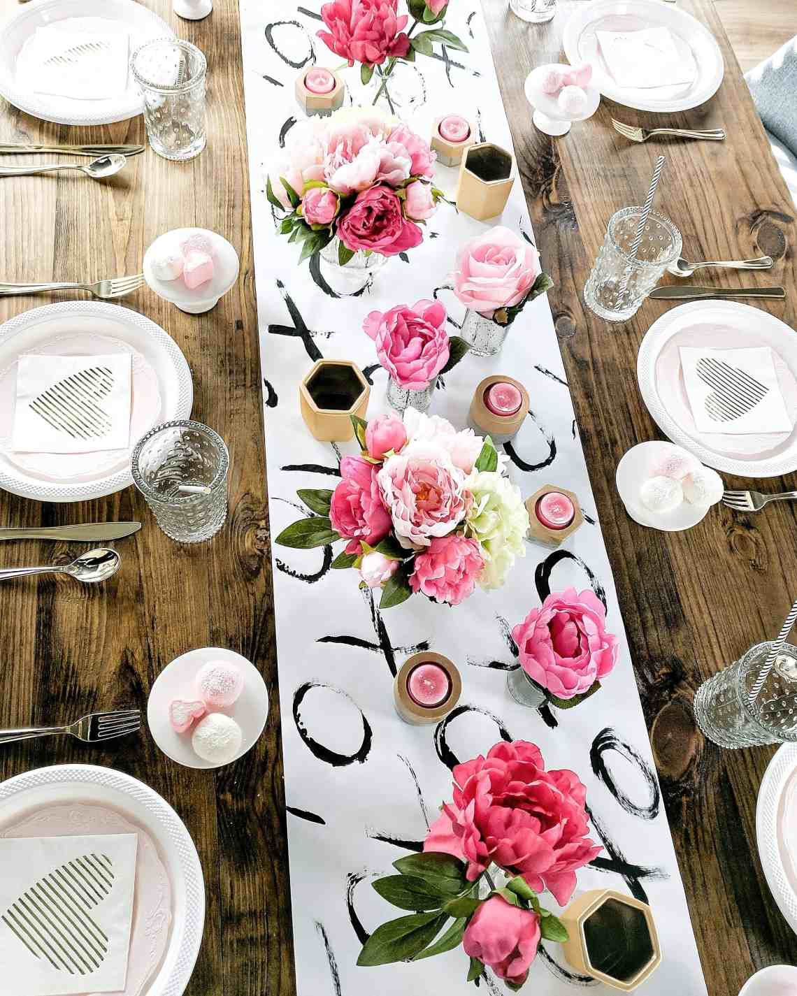 Table setting with wood table black and white table runner and floral and gold accents