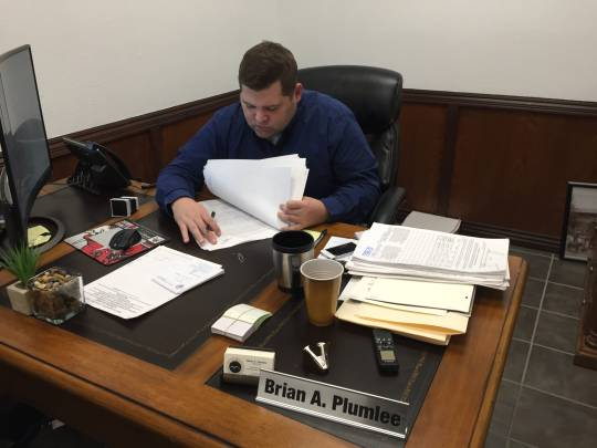 Mountain Home Clerk Brian Plumlee reviews several pages of signatures pertaining to a petition to permit Sunday off premise alcohol sales before stamping them