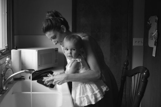 A mother washing the hands of her daughter. A microwave oven sits beside the sink for easy access.