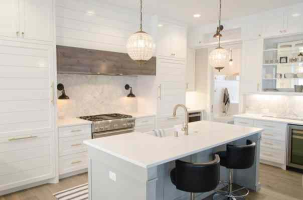 An island kitchen layout with a white theme. Chairs are positioned by the island counter for a more inviting feel.