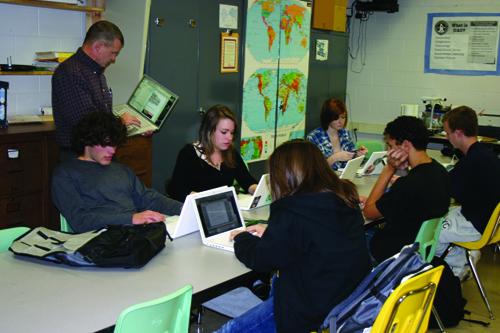 Government teacher Scott Yant instructs senior Mazlow Petosa, junior Sarah Payne, junior Jessica Harris and senior McKenzie Masters at the community school. Each student in the community school is lent a laptop for the school year.