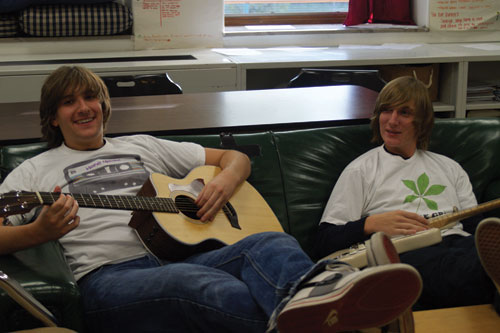 Seniors Jamie Vaughn (left) and Ben Berens sport Home Grown clothing merchandise while Vaughn plays his guitar.  The duo have decided to work for themselves rather than seeking a job in a store or restaurant.