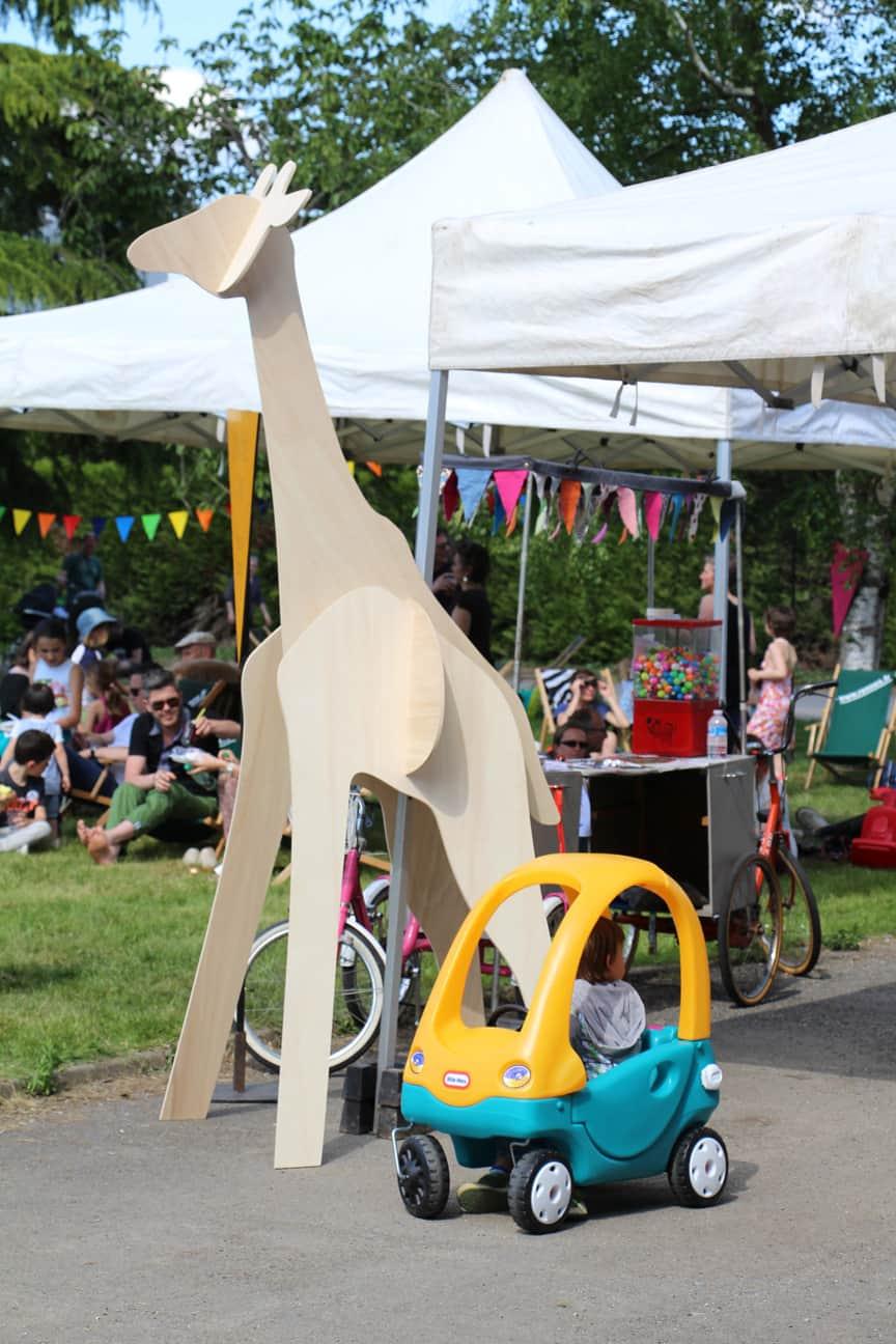 Photo La girafe en bois avec, à ses pieds, un enfant dans une voiturette