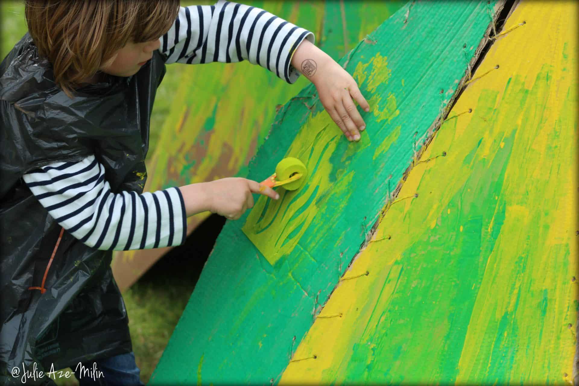 Photo La Fête #6 - atelier arts plastiques - un enfant peint sur un carton
