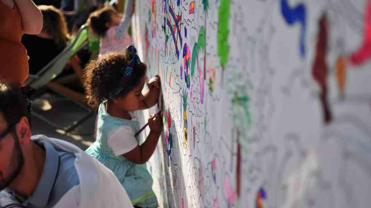 Photo d'une petite fille dessinant sur une fresque murale - Le Hasard Ludique