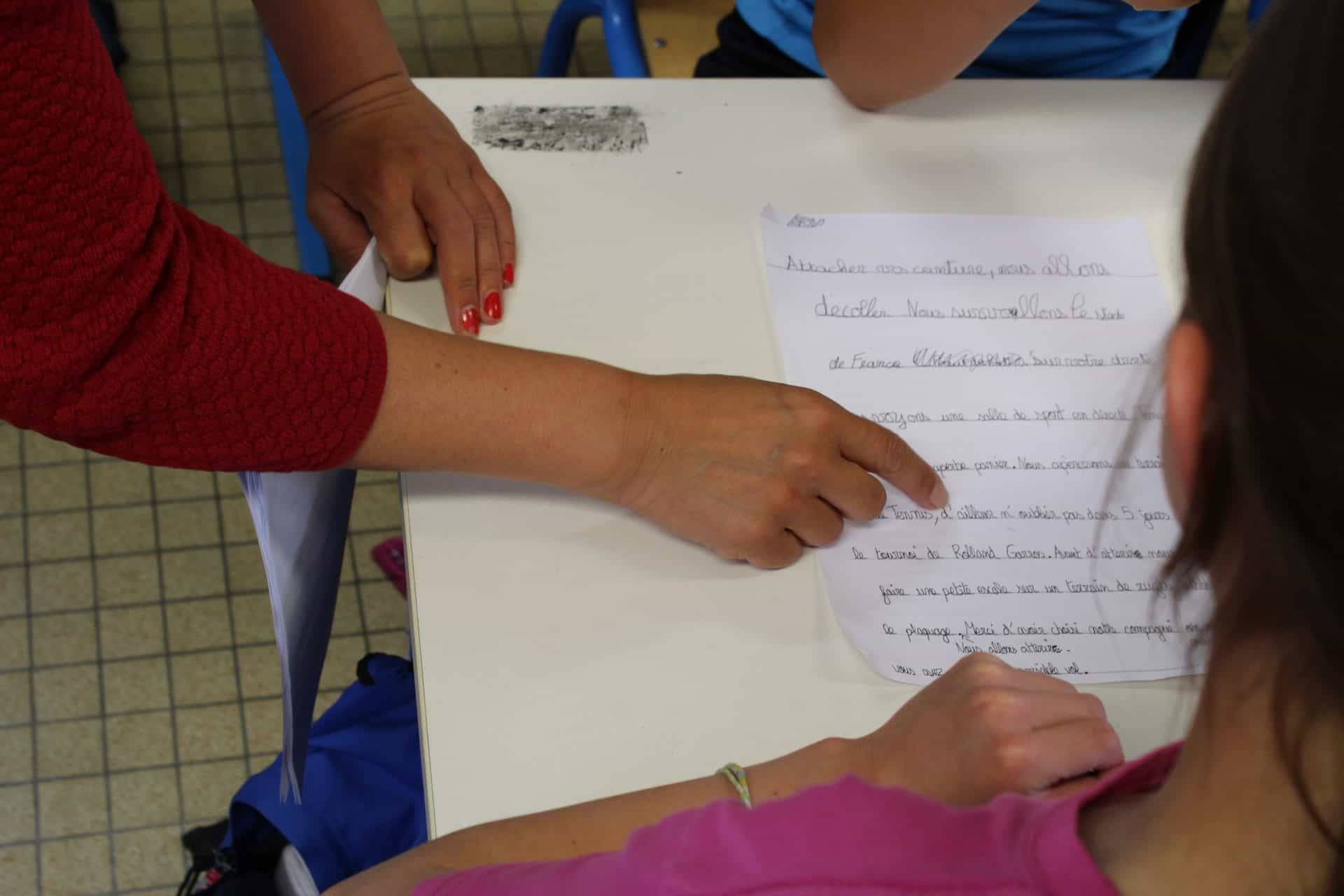 Photo - une enfant écrit un texte avec une adulte