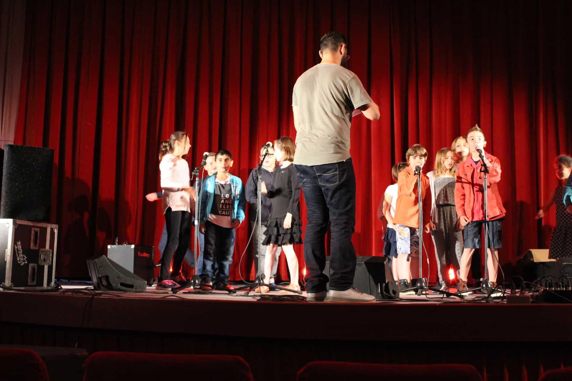 Photo - un groupe d'enfants est sur scène devant des micros