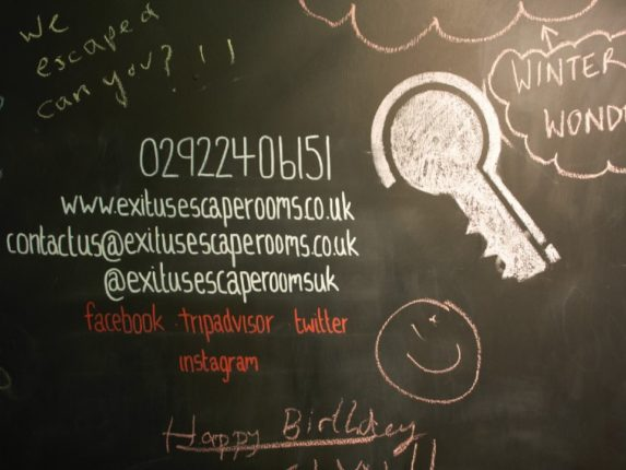 Chalkboard writing showing contact details for Exitus Escape Rooms.