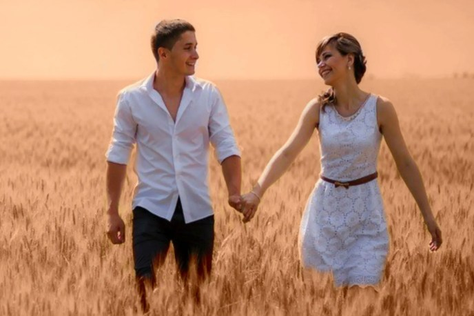 happy couple walking through a field