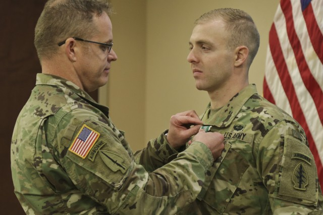 Sgt. Maj. William Barr (Left) with United States Army Special Operations Command, awards Spc. Seth Ravid (Right) with 4th Battalion, 7th Special Forces Group (Airborne) an Army Commendation Medal during an AG Corps brief at the 7th SFG(A)'s Auditorium Jan. 27, 2017 on Eglin Air Force Base, Florida. Spc. Ravid won the USASOC level AG Corps Soldier of the Year competition at Fort Bragg and is slated to compete at the Army-level competition at Fort Jackson in June. (U.S. Army photos by Staff Sgt. Brian K. Ragin Jr.)