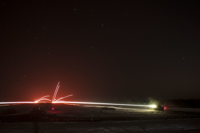 BMP-2 armored vehicles from the Ukrainian army's 1st Battalion, 28th Mechanized Infantry Brigade engage targets after nightfall on Feb. 16 while training at the International Peacekeeping and Security Center, near Yavoriv, Ukraine.