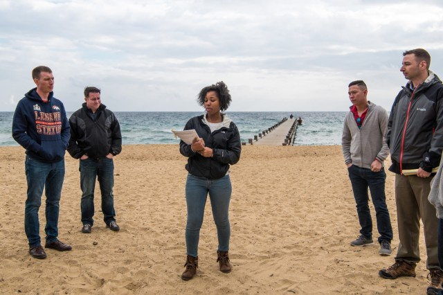 CAVALAIRE BAY, France - Standing on Alpha Red beach, Capt. Keisha M. Henry, intensive care and flight nurse, 212th Combat Support Hospital, briefs fellow leaders about the courageous actions that earned Staff Sgt. Audie Murphy the Distinguished Service Cross during Operation Anvil - Dragoon, Feb. 27, 2017. (U.S. Army Photo by Maj. Chris Angeles, 67th Forward Surgical Team)