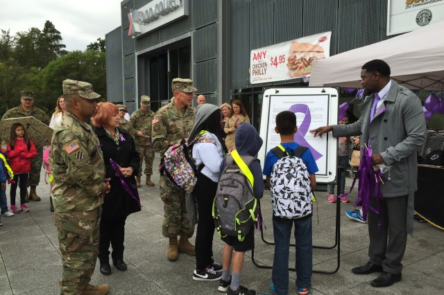 From center in uniform, the garrison commander Col. Glenn K. Dickenson, deputy to the garrison commander Heidi M. Malarchik and Command Sgt. Maj. Mariano Z. Alvarez visit a display for domestic violence awareness.