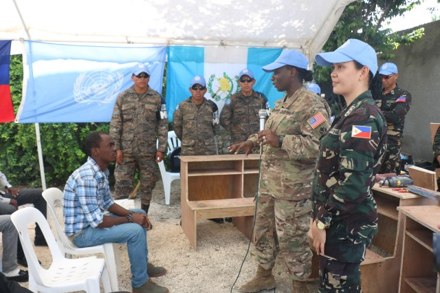 Maj. Windy Waldrep, MINUSTAH civil-military coordination officer, speaks at an event for International Peacekeeping Day, May 28, 2016. During the event, soldiers with the Philippine contingent taught students carpentry skills.