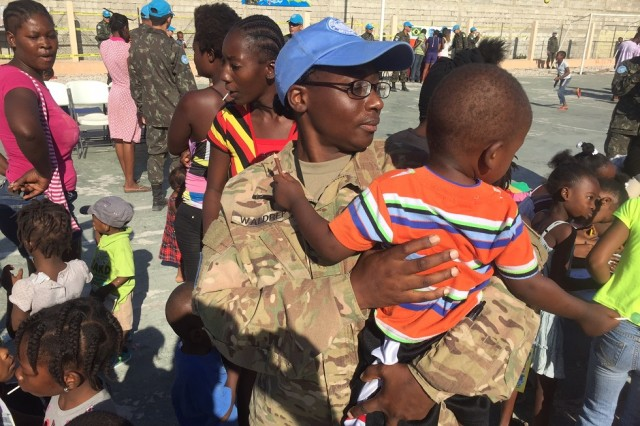 Maj. Windy Waldrep interacts with children at a holiday event for children hosted by MINUSTAH's Brazilian Battalion in Cite Soleil, Dec. 23, 2016. Activities included coloring books, soccer, martial arts demonstrations, jump rope and other games.