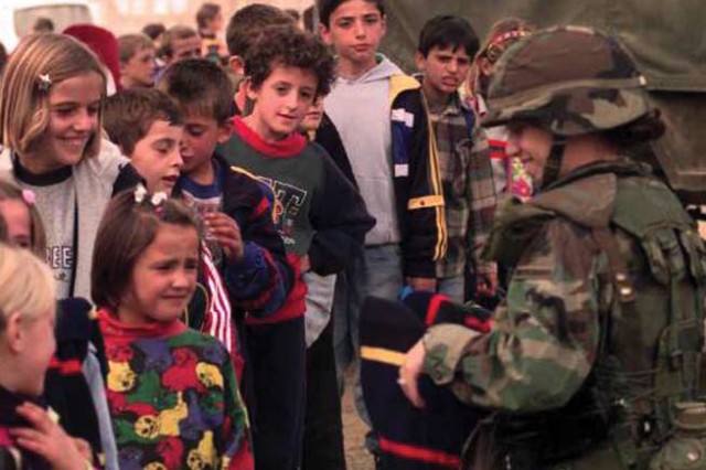 U.S. Army personnel distribute school supplies, winter clothes, and mine-awareness packages to Albanian children in a small town in MNB-East.