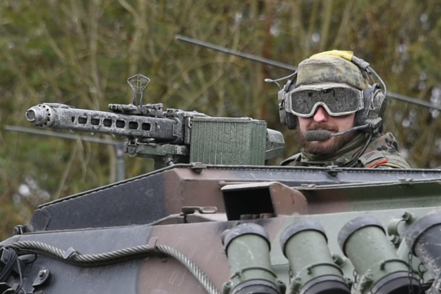 A Germany soldier in the 131st Artillery Battalion scans Grafenwoehr Training Area's terrain during Dynamic Front II, an artillery operability exercise that tests multinational interoperability at the tactical level.