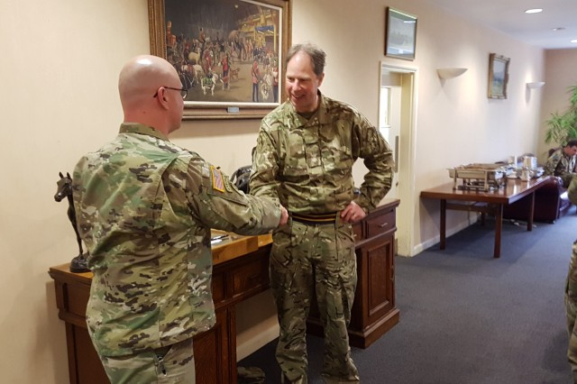 Col. Steve Greiner, Public Health Command Europe commander, presents a unit coin to Lt. Col. Mark Morrison, the Defence Animal Centre commanding officer, during the visit.