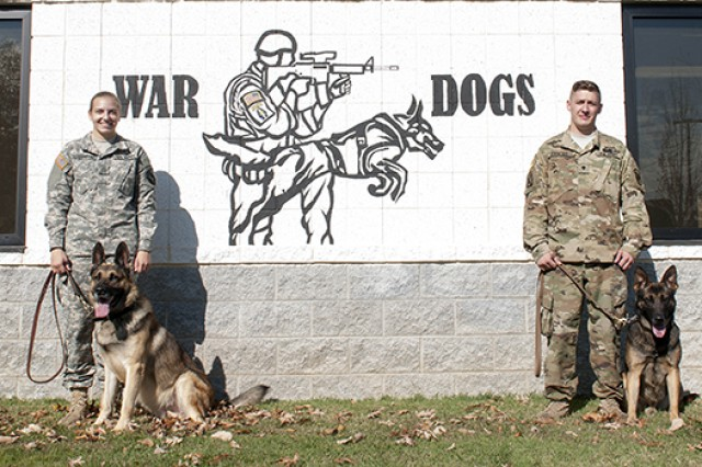Army PFC Sadie Vollendorf and her dog, Ricky, pose with Spc. Michael Finochio and dog Izmos outside the Fort Belvoir Kennels.