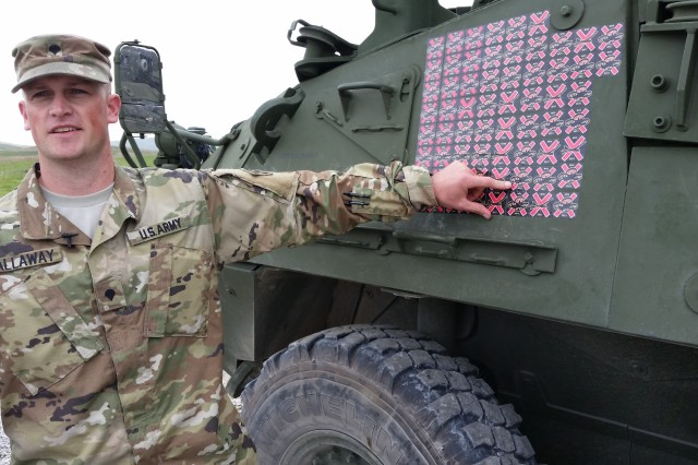 Spc. Brandon Sallaway, a fire support specialist and forward observer from Fort Carson, Colo., points to a sticker on the side of the Mobile High-Energy Laser-equipped Stryker he helped evaluate, April 12, at the 2017 Maneuver Fires Integrated Experiment at Fort Sill, Okla. The stickers represent the number of drones the MEHEL has shot out of the sky using a 5kW laser. Sallaway was the first Soldier to actually use the MEHEL to take down a target.