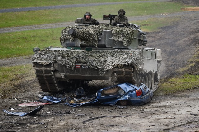 An Bundesheer Leopard 2A4 tank crushes car as part of the precision driving lane, during the Strong Europe Tank Challenge at the 7th Army Training Command's Grafenwoehr Training Area.