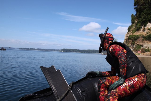 "A safety swimmer keeps on eye on a team from 3rd Battalion, 1st Special Forces Group (Airborne) during a competition held during ""Dragon Week"" on Joint Base Lewis-McChord, Wash., June 28. Dragon Week consisted of airborne operations, maritime operations, patrol lanes, a stress shoot, and medical evaluations to test readiness at the battalion level."