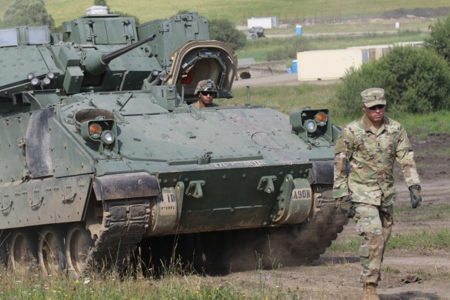 A Soldier from 1st Battalion, 66th Armor Regiment, 3rd Armored Brigade Combat Team, 4th Infantry Division, ground-guides an M2A3 Bradley Fighting Vehicle to a maintenance area July 1, 2017, at the Cincu Joint Multinational Training Center in Cincu, Romania, where the brigade will participate in the U.S. Army Europe-led multinational exercise Getica Saber 17. Getica Saber is a U.S.-led fire coordination exercise and combined-arms live fire exercise being held from July 8-15 to highlight participant deterrence capabilities, specifically the ability to mass forces at any given time anywhere in Europe. Besides the 3rd ABCT, 4th Inf. Div., Getica Saber will feature the Romanian 282nd Mechanized Brigade, the U.S. 1st Cavalry Division Artillery and service members from Croatia, Ukraine, Portugal, Montenegro and Armenia. (U.S. Army photo by Staff Sgt. Ange Desinor, 3rd Armored Brigade Combat Team, 4th Infantry Division Public Affairs)