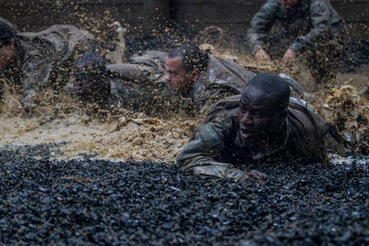 U.S. Army Soldiers in Basic Combat Training low crawl through the final obstacle during the Fit to Win endurance course at Fort Jackson, S.C.
