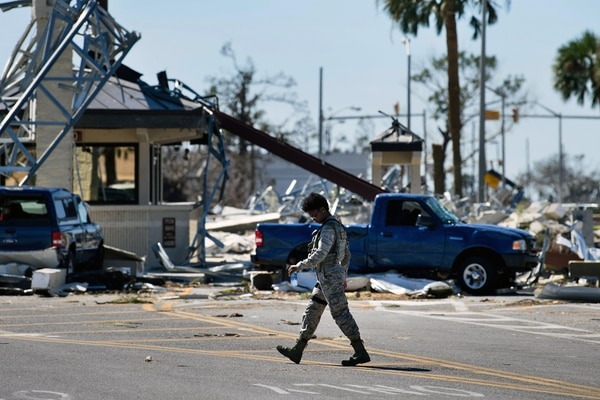 A military police officer walks near a destroyed gate in Tyndall Air Force Base, Fla., in the aftermath of Hurricane Michael on Oct. 12, 2018. (Brendan Smialowski/AFP via Getty Images)