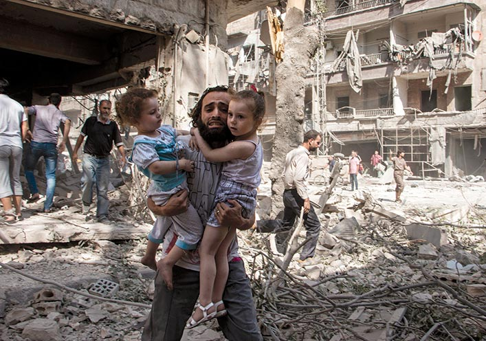 A Syrian man carries his two girls to safety 7 September 2015 across the rubble caused by a barrel bomb attack on the rebel-held neighborhood of al-Kalasa