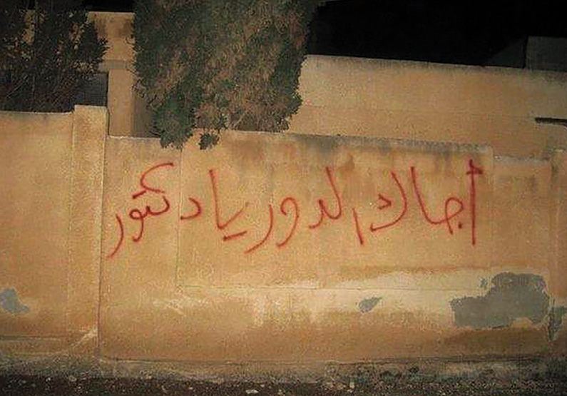 """This graffiti, written on a school wall in Daraa, Syria, February 2011 reputedly by then fourteen-year-old Naief Abazid, says """"Your turn, Doctor."""" The graffiti referred to the fall of Zine El Abidine Ben Ali of Tunisia and Hosni Mubarak of Egypt, and it implied that Syrian dictator Bashar al-Assad was next. In response, the government arrested and tortured Abazid and twenty-two other boys, prompting violent protests across Syria and sparking the war against Assad that continues today. (Photographer unknown)"""